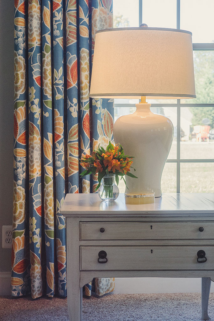 Flowered curtain panel behind cream lamp and light gray end table