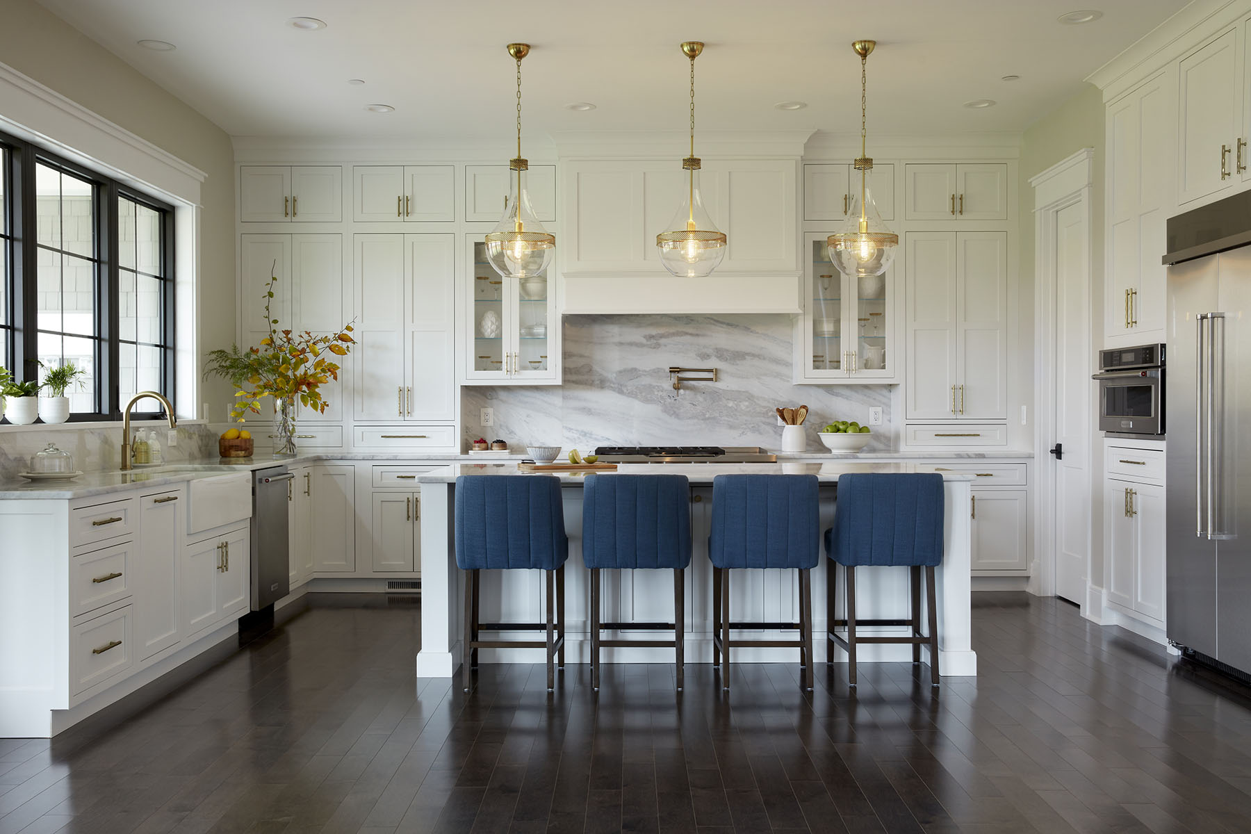 Modern white kitchen with gold fixtures and navy stools